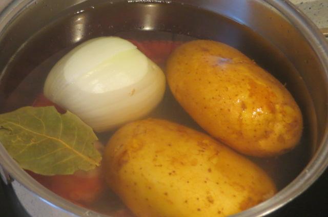 cociendo las patas de pulpo, las patatas y la cebolla