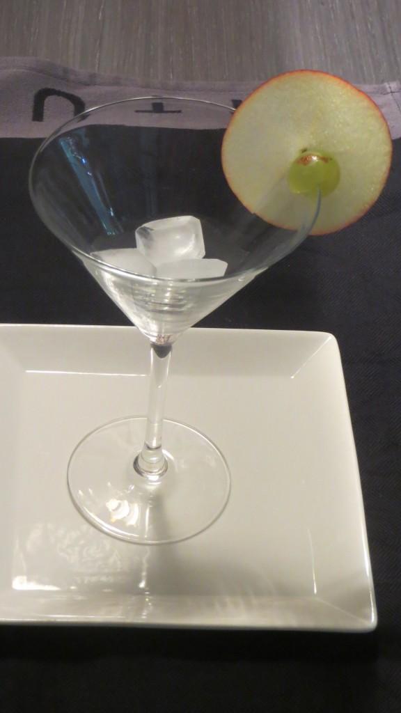 manzana y uva colocadas en el borde de la copa