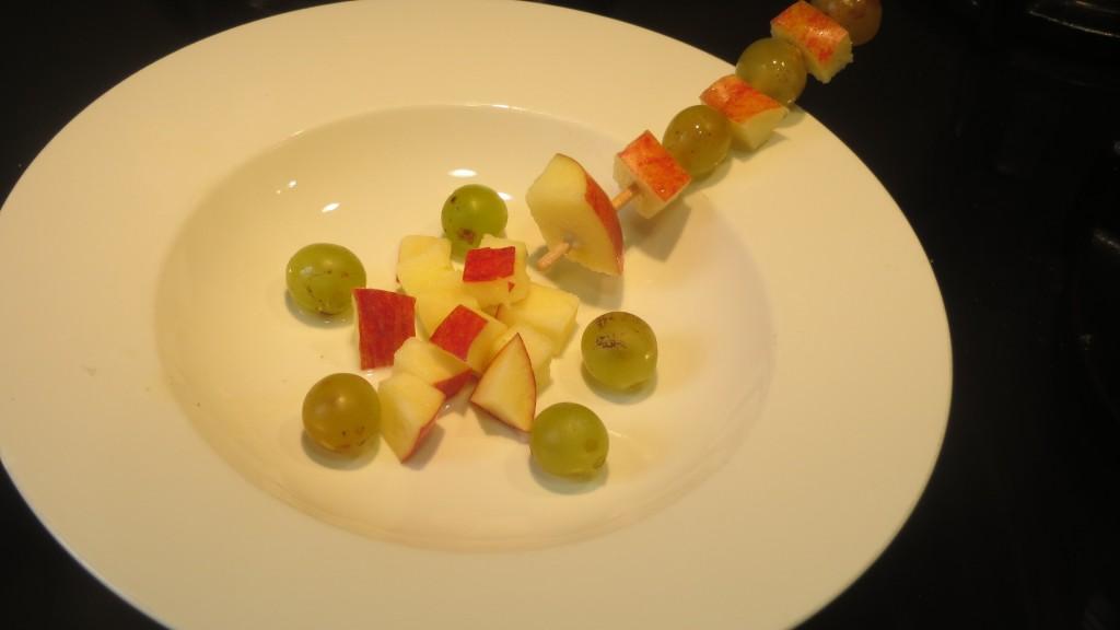 dados de manzana, uvas y brocheta colocadas en el plato
