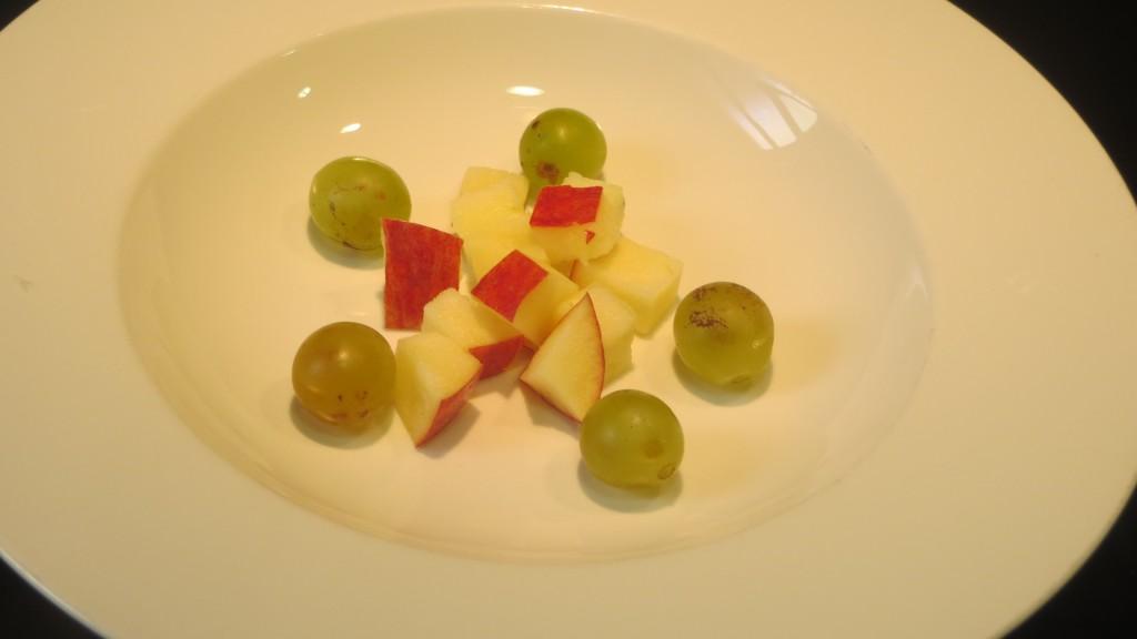 manzana cortada y uvas colocadas en el plato