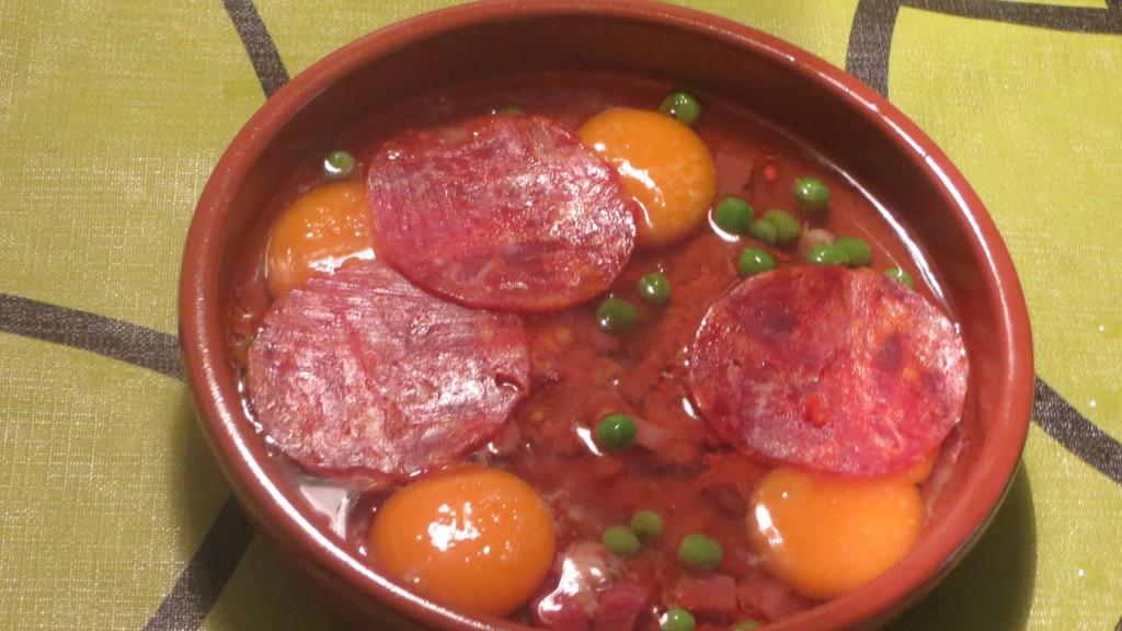 añadiendo las rodajas de chorizo encima de los huevos