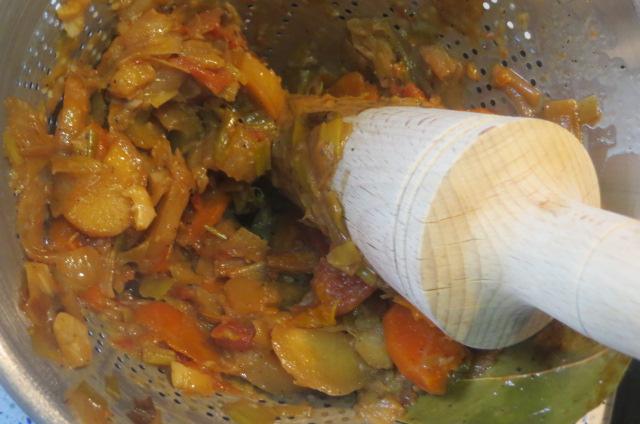 apretando las verduras contra las paredes del colador