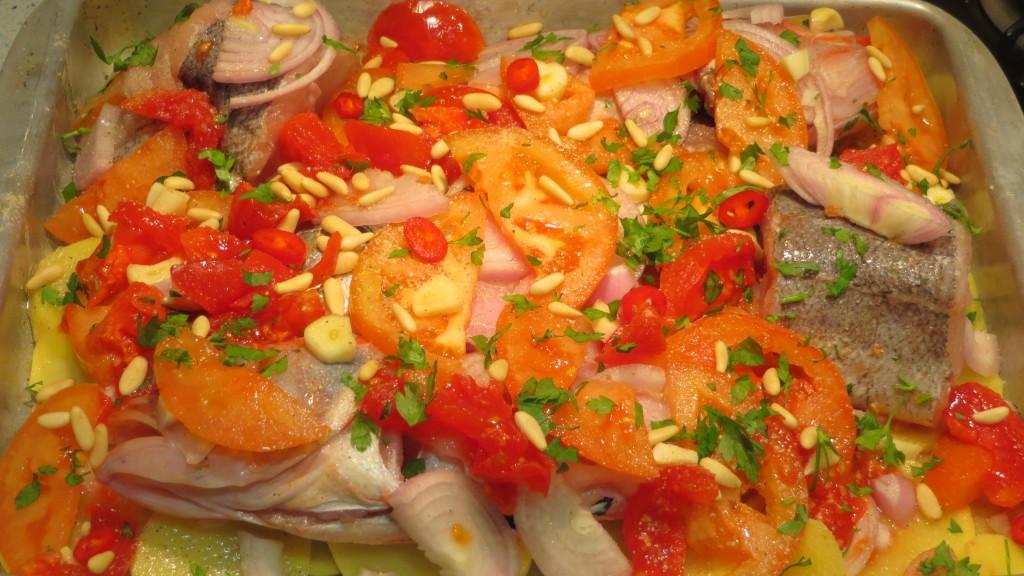 piñones, ajos, guindilla y perejil sobre los tomates y pescados