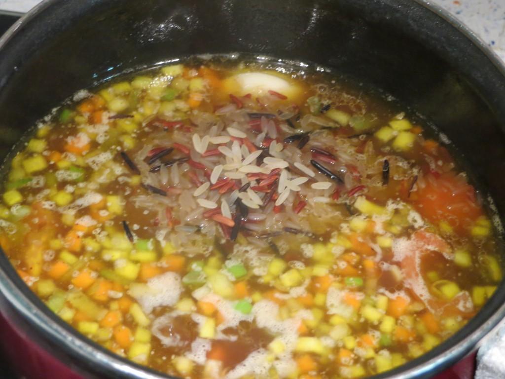 incorporación de la variedad de arroces al caldo de ave con verduras