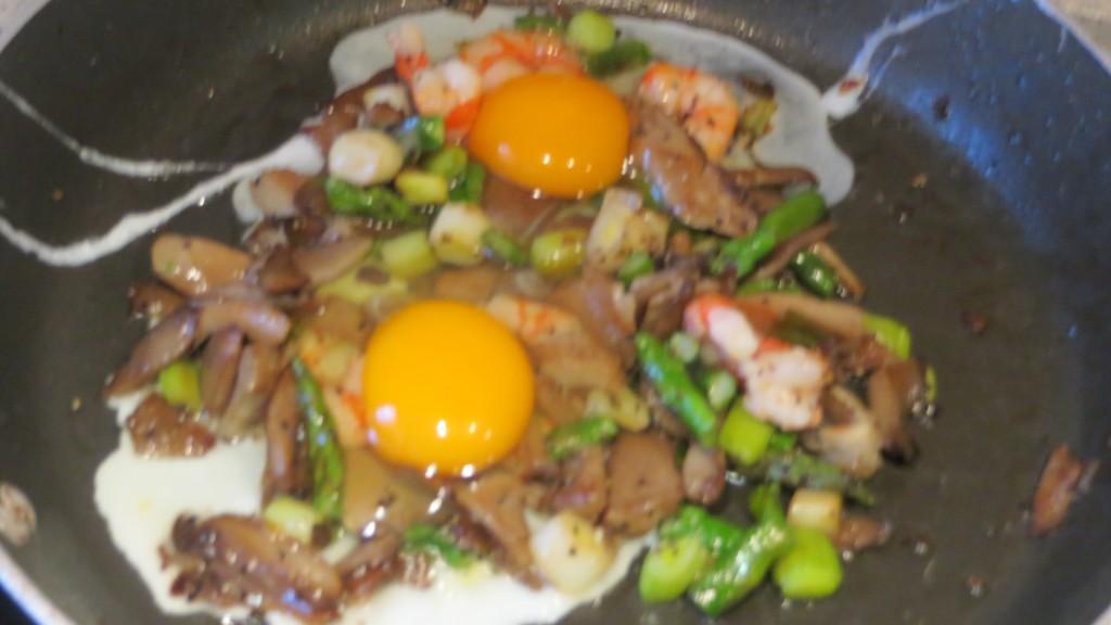 huevos incorporados al revuelto de ajos tiernos, espárragos, setas y gambas