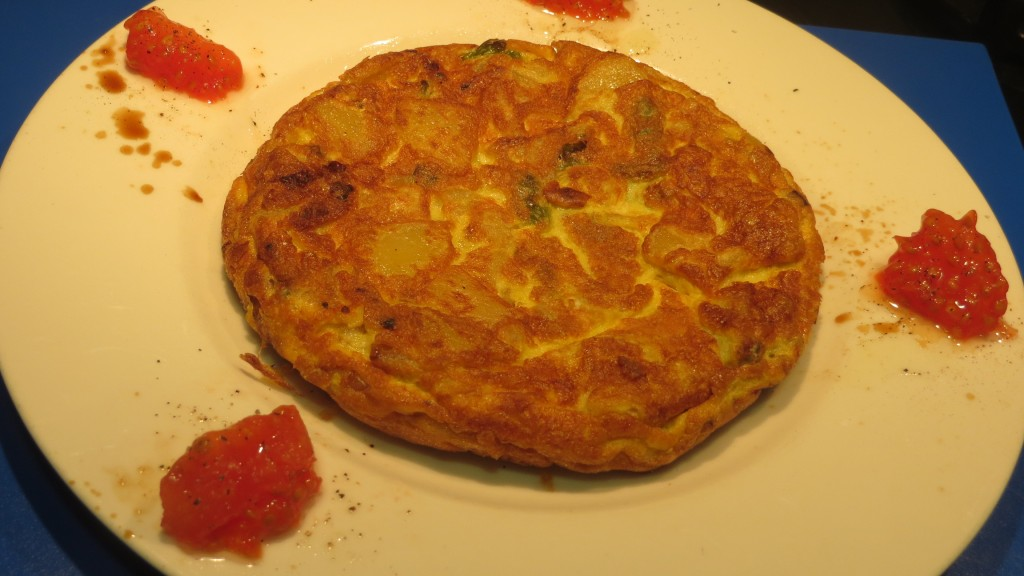 tortilla de patata con cebolla y pimiento verde acompañada de flores de tomate