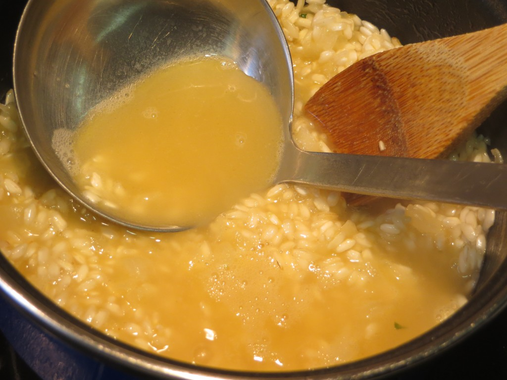 incorporación de un cucharón de caldo al arroz