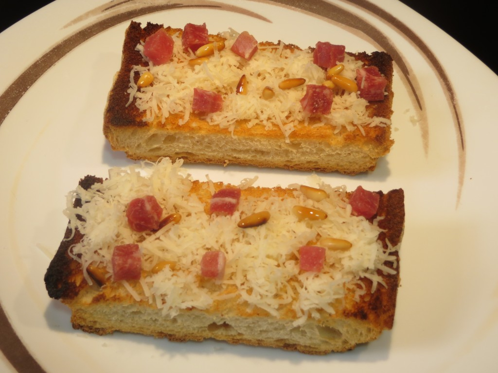 queso, jamón y piñones sobre la superficie del pan