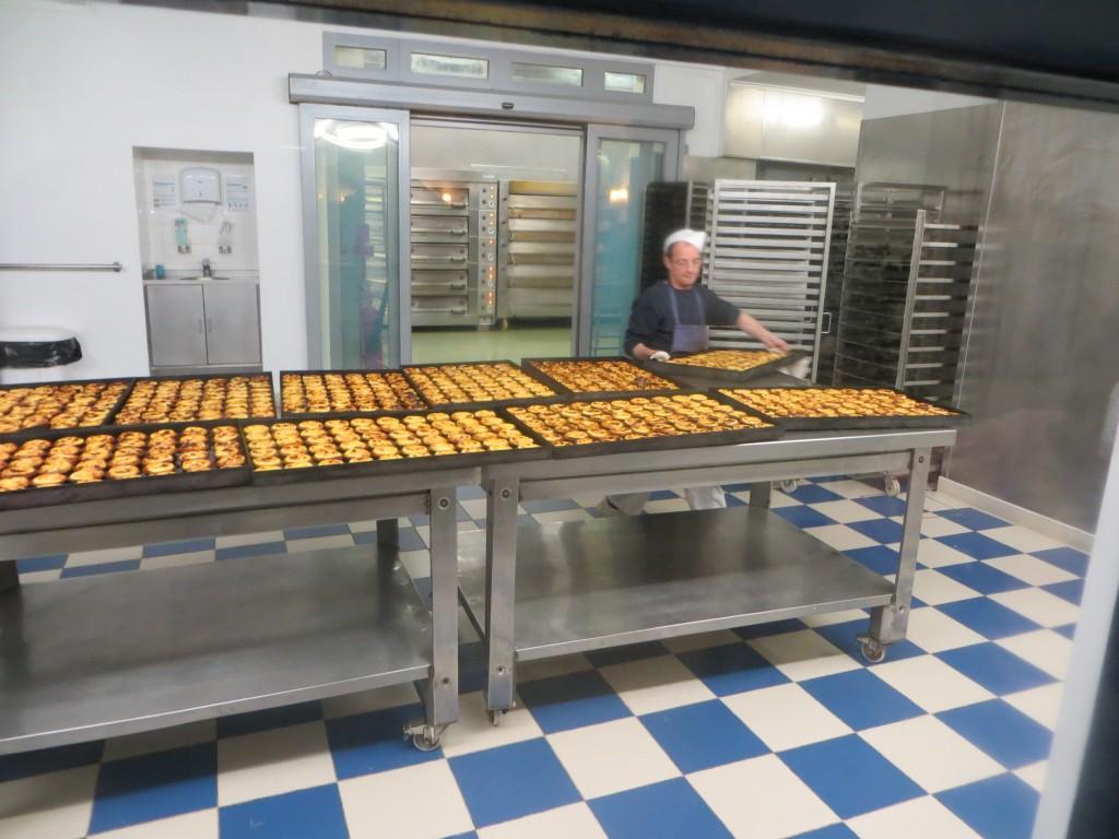 operario colocando bandejas de pasteles de Belém