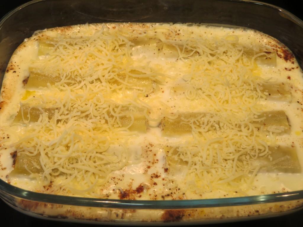 queso rallado esparcido sobre la salsa besamel