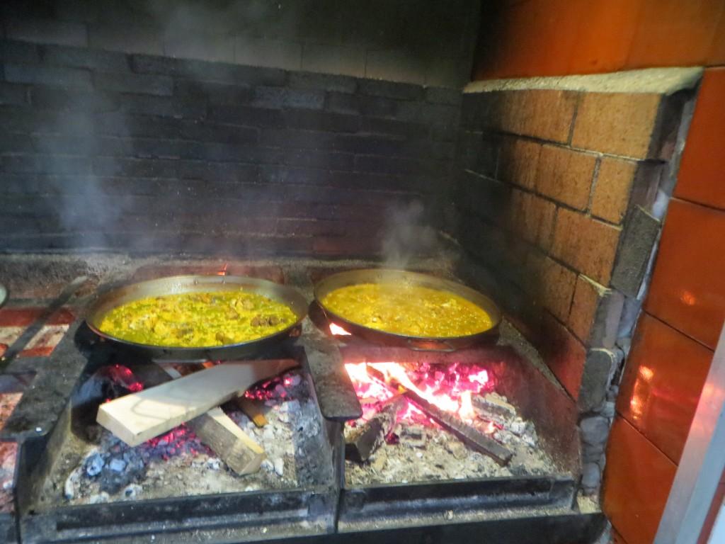 paellas cocinándose sobre fuego de leña de naranjo