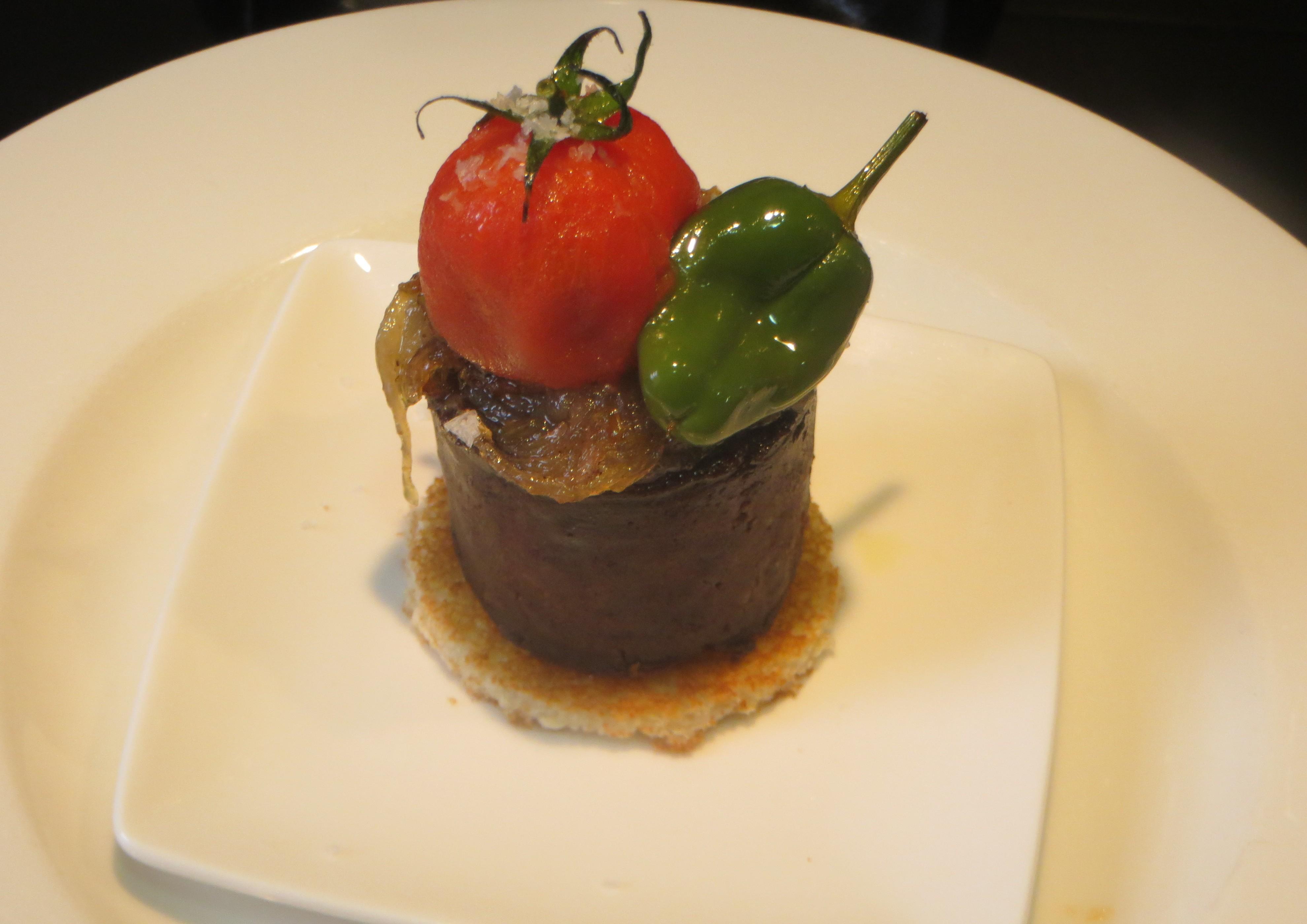 pincho de morcilla con cebolla caramelizada, tomate cherry y pimiento de Padrón