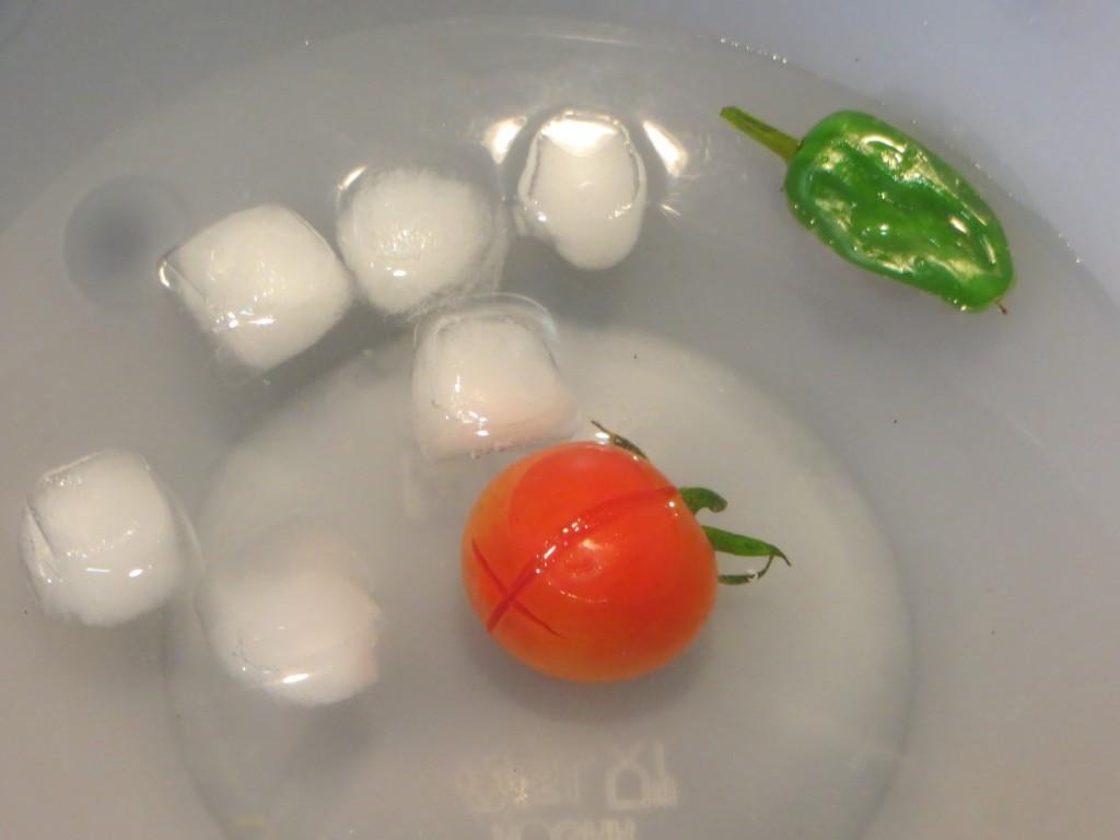 tomate cherry y pimiento de Padrón sumergidos en agua con hielo