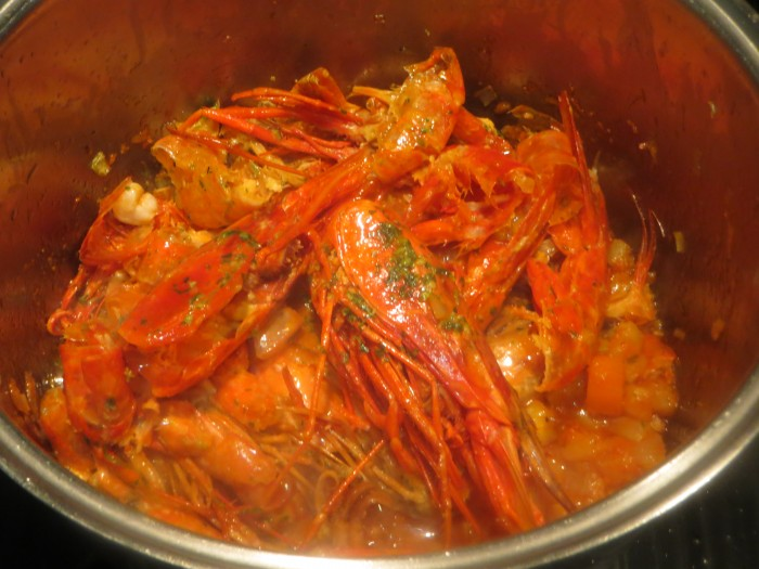 restos de crustáceos rojos incorporados al sofrito